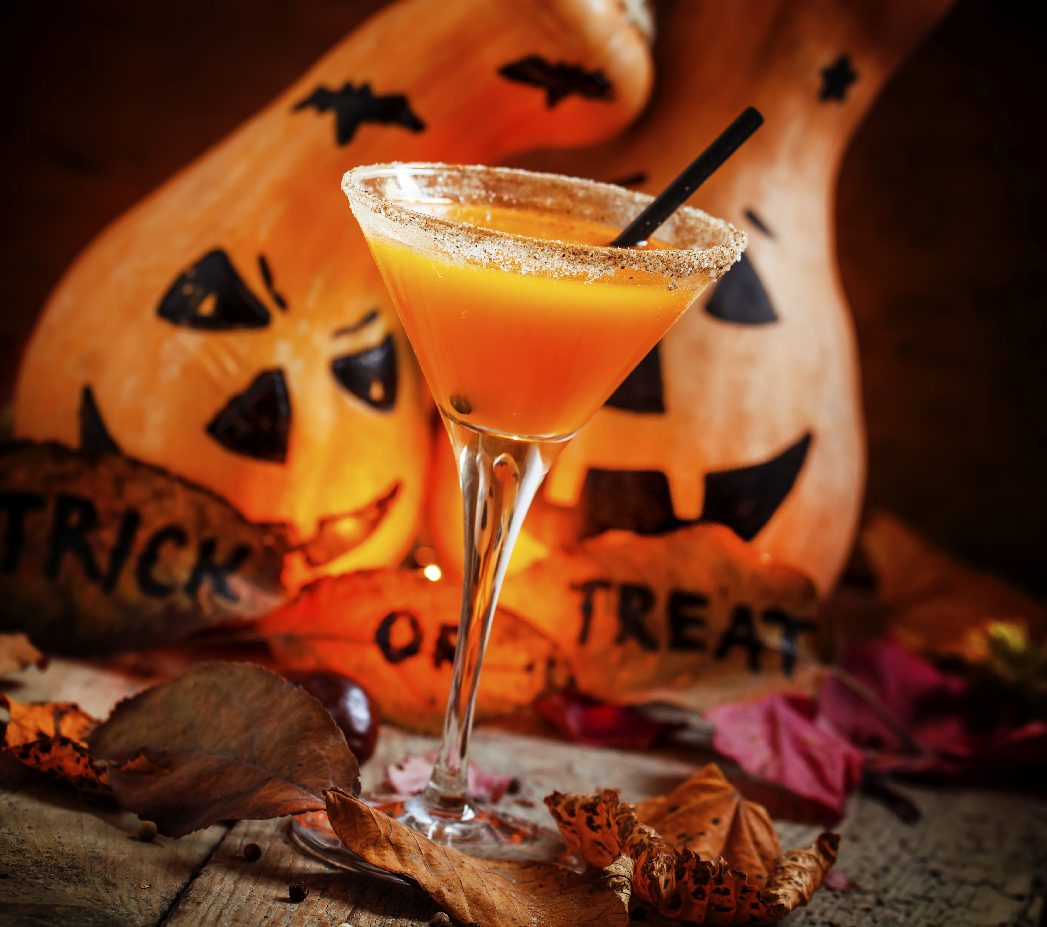 Orange Halloween cocktail and holiday pumpkins on a dark mystical autumn background, selective focus